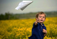 boy throwing paper airplane